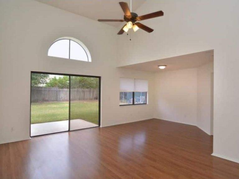beau salon avec parquet et une grande porte fenêtre