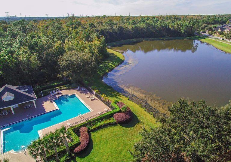 vue du ciel d'une villa avec piscine proche d'un lac