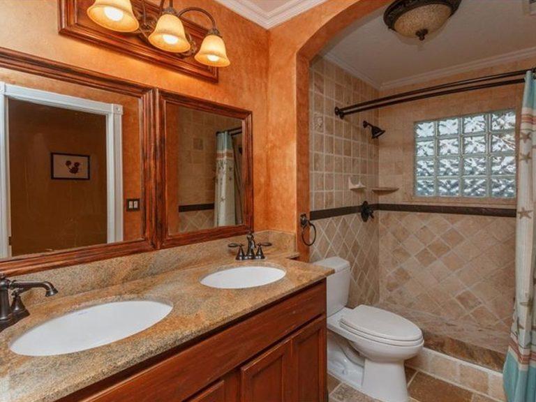 Voici une salle de bain de type rustique avec deux vasques et une douche à l'italienne