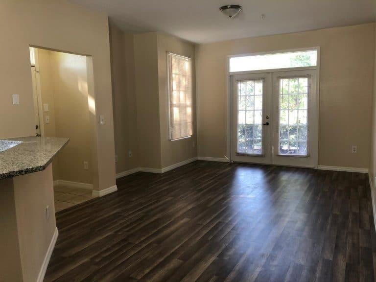 salon avec baie vitrée et parquet au sol